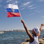 epaselect epa04332525 A local boy waves a Russian flag during the annual Russian Navy Day parade in Sevastopol, Crimea, 27 July 2014. The Russian Black sea fleet is based in the city of Sevastopol, annexed by Russia, in the Ukrainian peninsula of Crimea. EPA/ANTON PEDKO